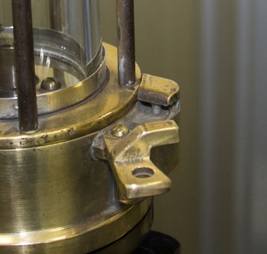 A close up of the magnetic lock on a miners' lamp showing the catch arm and spring-loaded pin.