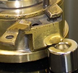 A close up of the magnetic lock on a miners' lamp showing the catch arm and spring-loaded pin released using a strong magnet.