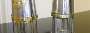 A pair of miners' safety lamps. Left: Regular lamp with magnetic lock. Right: Deputy's lamp.