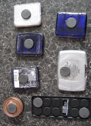Magnetic make-up organiser showing items of make-up stuck to a metallic tray using ferrite disc magnets