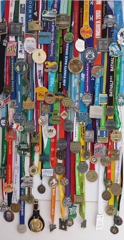 100 running medals attached to a ferrous board with magnets