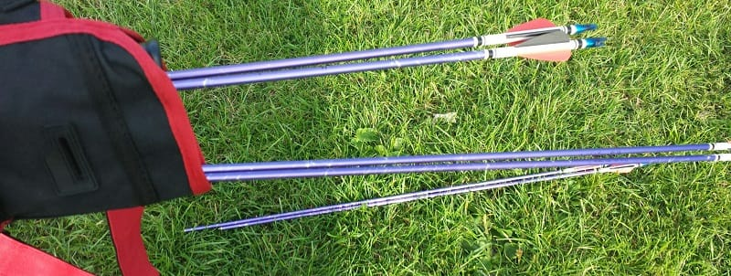 Aluminium archers' arrows and quiver lying on grass