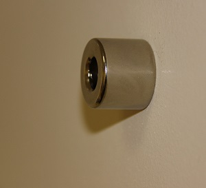 25mm diameter neodymium magnet attracting to studs in plasterboard wall.