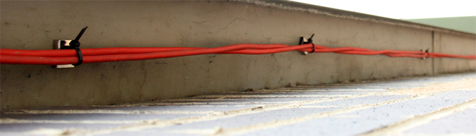 Magnetic cable tie mounts holding thick red cable to underside of a steel gurder