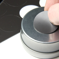 Sticking self-adhesive magnet on to favour tin